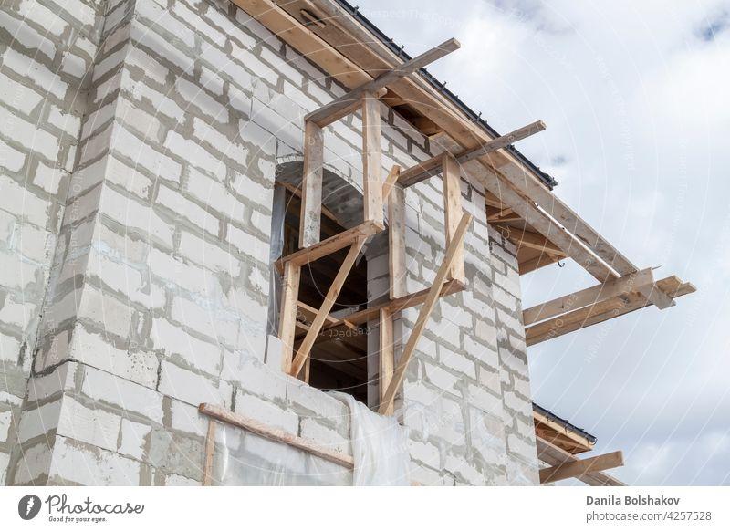 Nahaufnahme eines Gerüsts und eines im Bau befindlichen Hauses mit Halterungen für die Dachrinnen und das Wasserabflusssystem Wasserrinne Installation