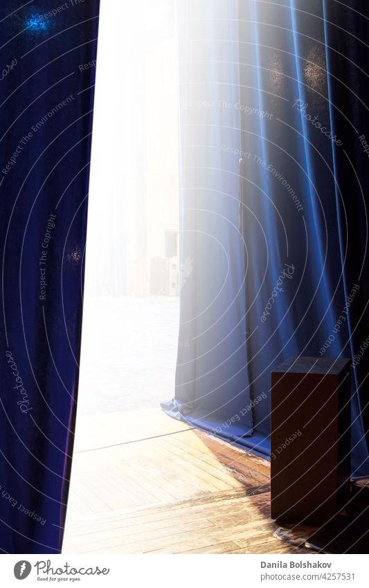 Blick auf die hell erleuchtete Bühne von hinter dem Vorhang Gardine blau Schauplatz Theater hinten offen Kino Licht Hintergrund Seile theatralisch weiß