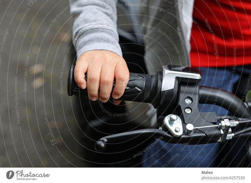 Kinderhand am Lenkrad eines Quads Fahrrad vierfach Spaß Rennen Motor Geschwindigkeit Sport Mitfahrgelegenheit Schmutz extrem aus Rad super aktiv Zyklus Junge