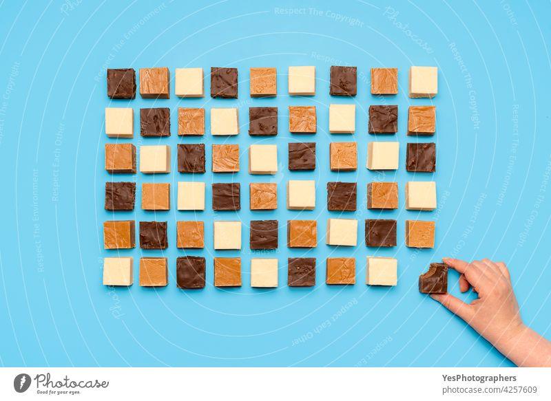 Fudge-Sortiment symmetrisch auf blauem Tisch ausgerichtet. Frau greift nach Schoko-Fudge, Ansicht von oben Überfluss Amerikaner Hintergrund Biss braun Bonbon
