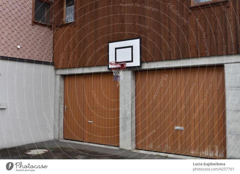 Basketballbrett und Basketballkorbnetz an der Wand des Familienhauses über zwei Garagentoren befestigt. sportlich Rückwand Hintergrund Holzplatte Konkurrenz