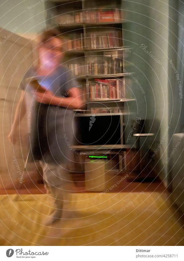 Verhuschte Frau mit Smartphone vor Fernseher und Bücherregal auf gelbem Teppich Kommunikation Wohnzimmer verwischt verhuscht