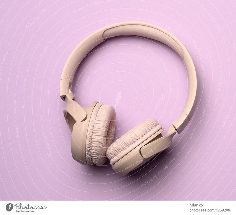 beigefarbene kabellose Kopfhörer auf einem lila Hintergrund Gerät Musik Personal stereo Audio Klang modern Atelier Technik & Technologie Headset digital zuhören