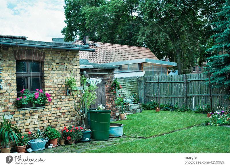 Ein Hinterhof  mit Blumentöpfen, Wäscheleine und Regenfass Gartenhaus Wiese Farbfoto Gras Zaun Sommer Nostalgie Fenster Gartenarbeit ruhig Idylle