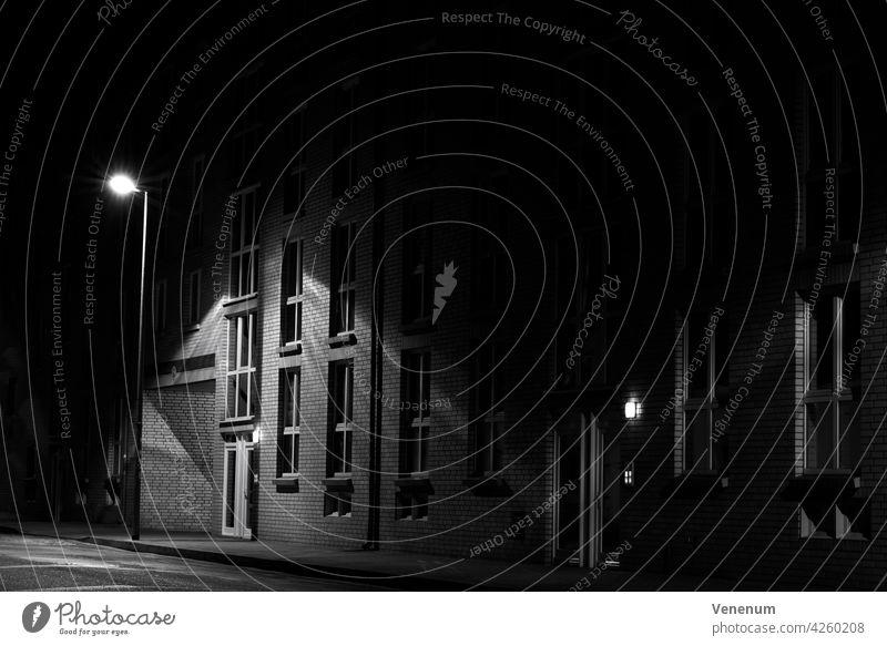 Nachts auf der Straße, Wohnhaus wird von Straßenlaterne beleuchtet, ohne Menschen, schwarz-weiß, Low Key Fotografie nachts Gebäude Baum Bäume Deutschland