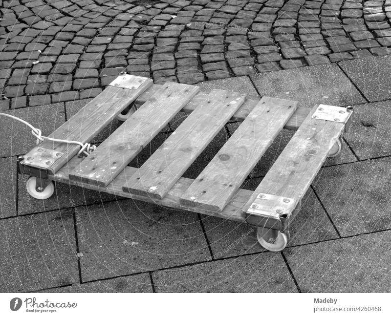 Angeleinte Holzpalette mit Rollen für den Transport von Kisten auf dem Wochenmarkt an der Bockenheimer Warte in Frankfurt am Main in Hessen, fotografiert in neorealistischem Schwarzweiß