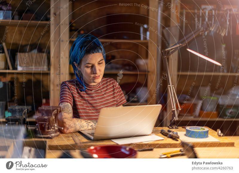 Junge Frau mit Laptop in ihrer Werkstatt diy Hipster Behaarung Tattoos Besitzer Beruf Dienst Kleinunternehmen Mitarbeiter arbeiten Arbeitsplatz Flugzeugwartung