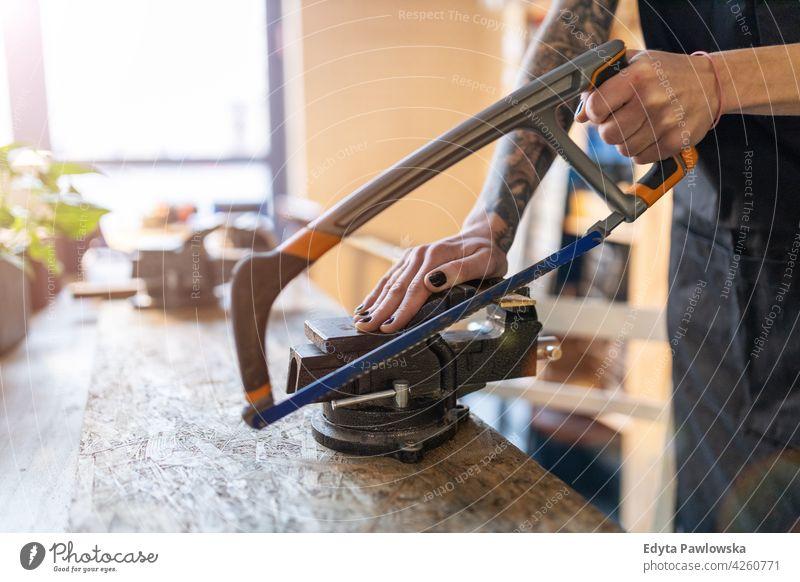 Frau mit Handsäge in ihrer Werkstatt diy Hipster farbenfroh Behaarung Tattoos Besitzer Beruf Dienst Kleinunternehmen Mitarbeiter arbeiten Techniker Arbeitsplatz