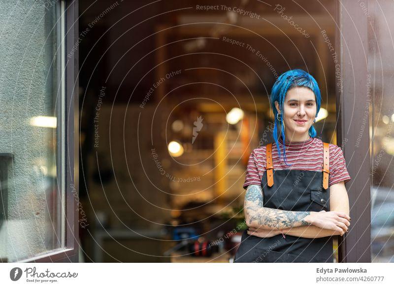 Selbstbewusste junge Handwerkerin in ihrer Werkstatt diy Hipster farbenfroh Behaarung Tattoos Frau Besitzer Beruf Dienst Kleinunternehmen Mitarbeiter arbeiten