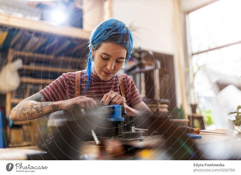 Junge Frau bei Holzarbeiten in einer Werkstatt diy Hipster Behaarung Tattoos Besitzer Beruf Dienst Kleinunternehmen Mitarbeiter Arbeitsplatz Flugzeugwartung