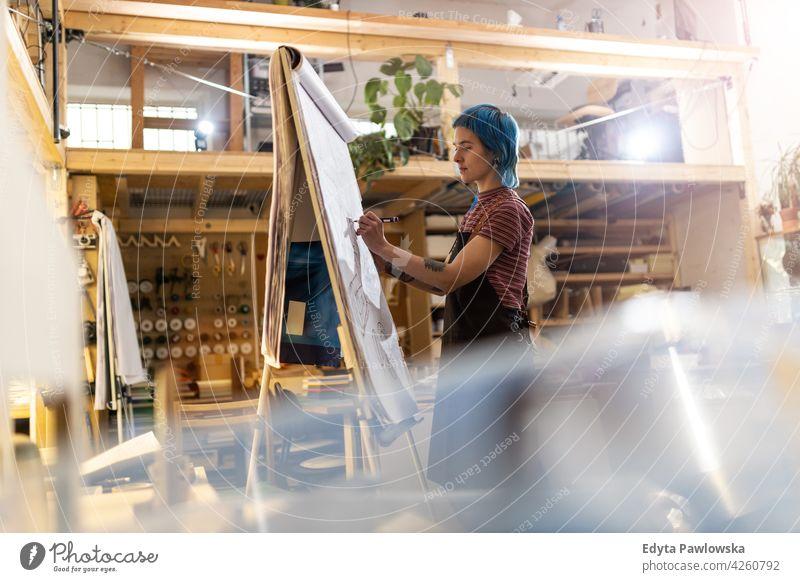 Weibliche Designerin beim Skizzieren ihres neuen Projekts in der Werkstatt diy Hipster farbenfroh Behaarung Tattoos Frau Besitzer Beruf Dienst Kleinunternehmen
