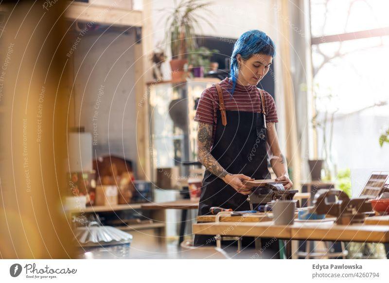 Zimmermannsfrau in ihrer Werkstatt diy Hipster Behaarung Tattoos Frau Besitzer Beruf Dienst Kleinunternehmen Mitarbeiter arbeiten Arbeitsplatz Flugzeugwartung