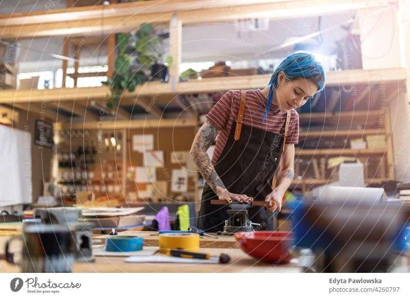 Junge Handwerkerin bei ihrer Arbeit diy Hipster Behaarung Tattoos Frau Besitzer Beruf Dienst Werkstatt Kleinunternehmen Mitarbeiter arbeiten Arbeitsplatz