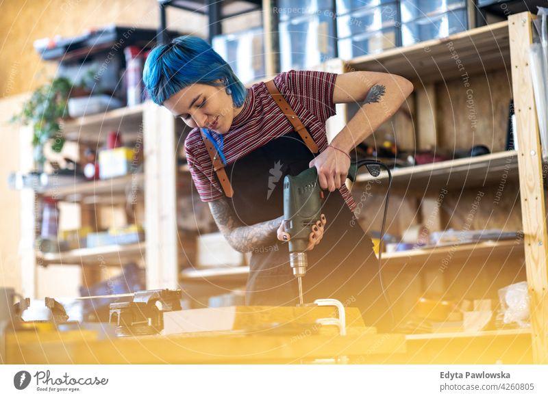 Junge Frau mit elektrischer Bohrmaschine in der Industriewerkstatt diy Hipster farbenfroh Behaarung Tattoos Besitzer Beruf Dienst Werkstatt Kleinunternehmen