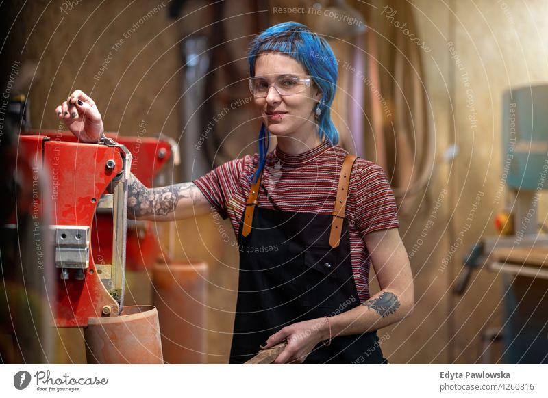 Zimmermannsfrau in ihrer Werkstatt diy Hipster farbenfroh Behaarung Tattoos Frau Besitzer Beruf Dienst Kleinunternehmen Mitarbeiter arbeiten Techniker