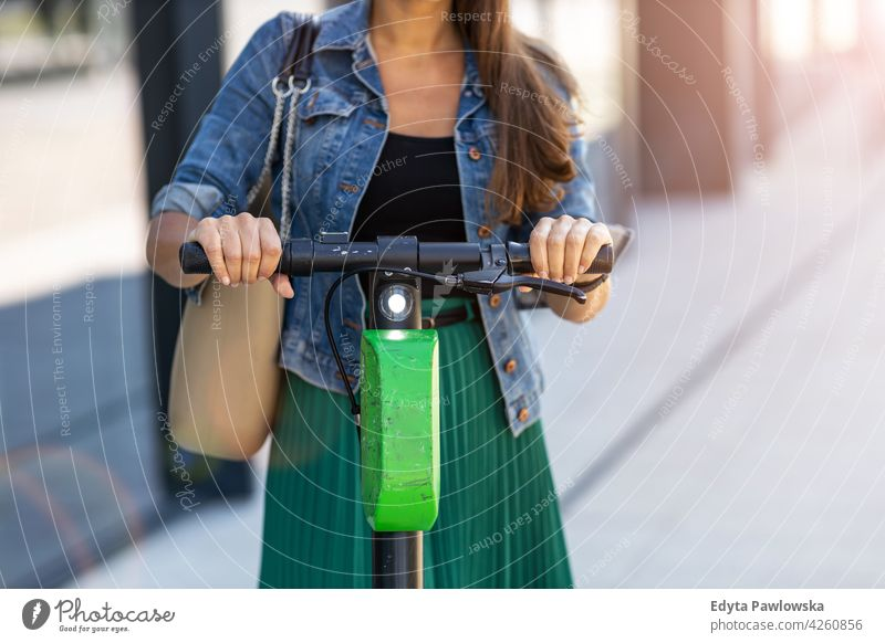 Weiblicher Pendler, der einen elektrischen Tretroller fährt urban Straße Großstadt aktiv Menschen Frau junger Erwachsener lässig attraktiv Glück Kaukasier