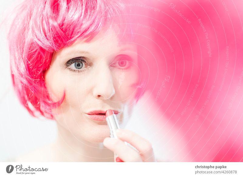 Frau mit pinker Perücke trägt Lippenstift auf Schminken Haare & Frisuren feminin Gesicht Spiegel Spiegelbild Kosmetik Junge Frau schön Mund Erwachsene Mensch