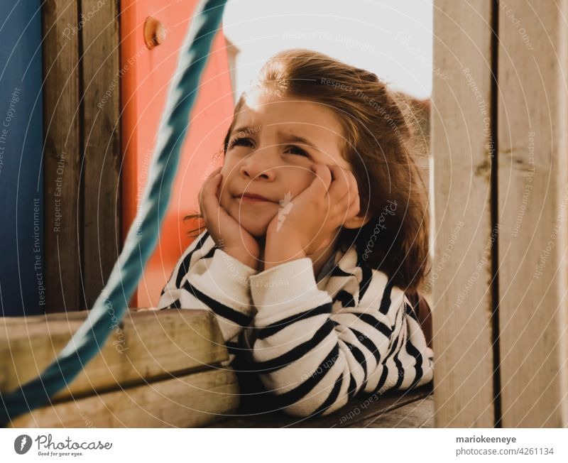 Porträt eines kaukasischen kleinen Mädchens mit den Händen auf dem Gesicht in einer nachdenklichen Haltung Unschuld Denken Ruhe Einsamkeit besinnlich