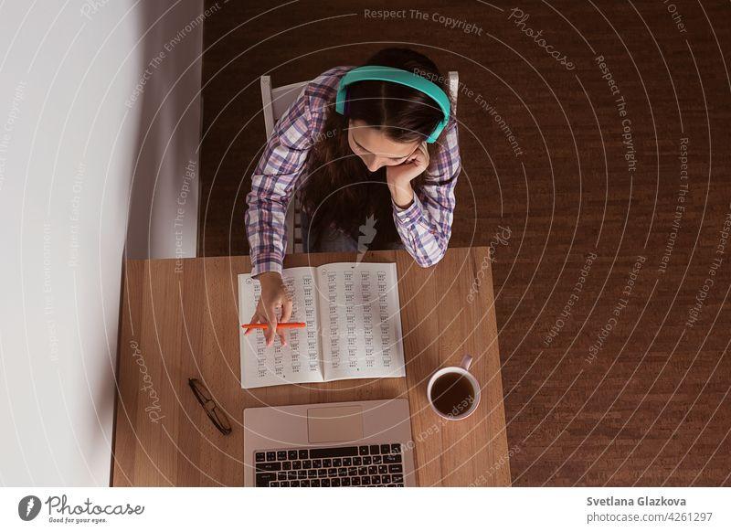 Student Laptop machen Notiz, hören Musik Kopfhörer und Buch lesen, Kaffee trinken. Elearning-Konzept Entfernung online Bildung Mädchen Frau Kind Kindheit