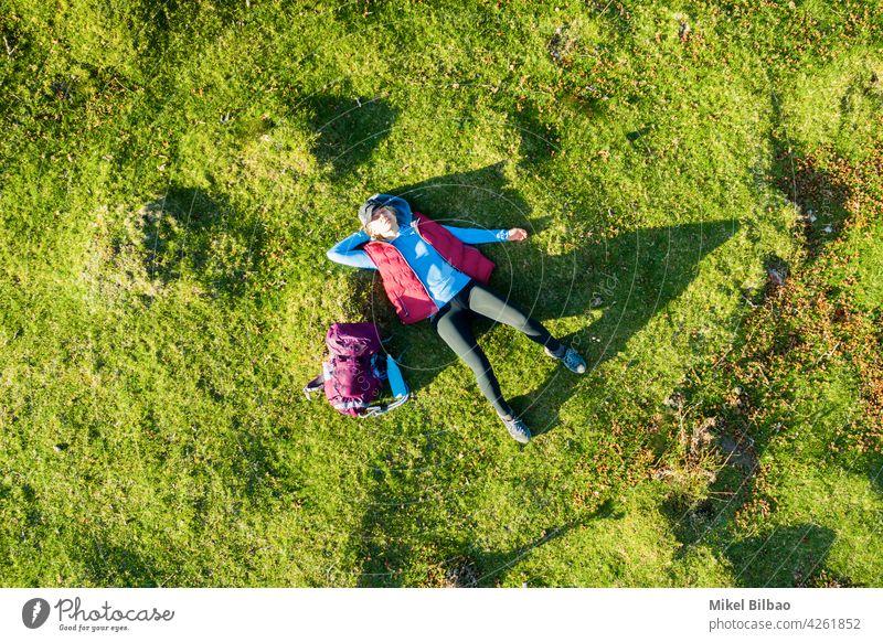 Luftaufnahme einer jungen Wanderin mit einem Rucksack auf dem Rücken liegend auf einer Wiese. Lebensstile Antenne Ferien Frau Wanderer Ausflug Spanien reist