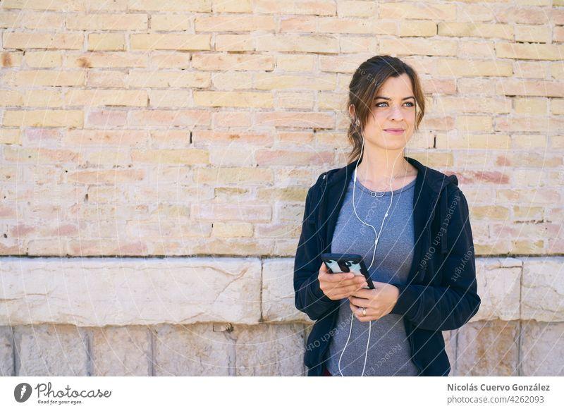 Junge Frau, die sich auf das Training vorbereitet und ein Mobiltelefon mit Kopfhörern benutzt Mädchen aktiv Kaukasier Sport Lifestyle Mobile hören Person