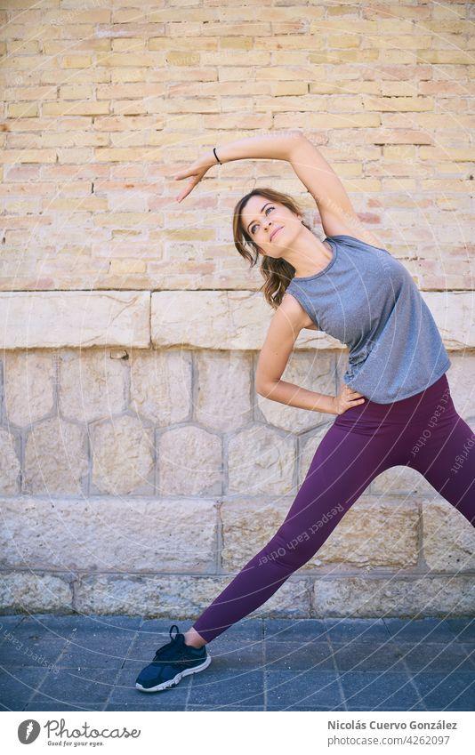Fitte, gesunde junge Frau beim Stretching auf der Straße. aktiv Kaukasier strecken Training urban attraktiv Gesundheit passen Textfreiraum Sportbekleidung