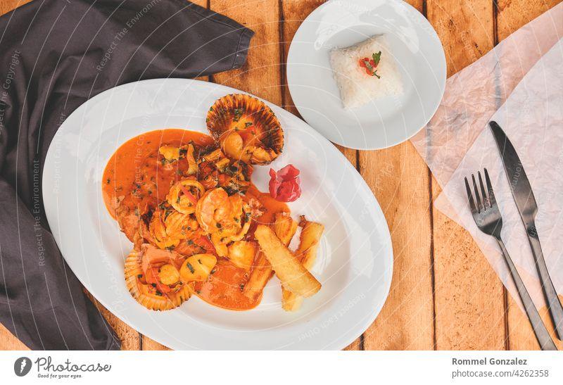 Peruanischer kulinarischer gebratener Fisch A lo Macho Art mit Meeresfrüchtesauce Restaurant Mahlzeit Peruaner Küche Reis Zitrone Gastronomie exotisch