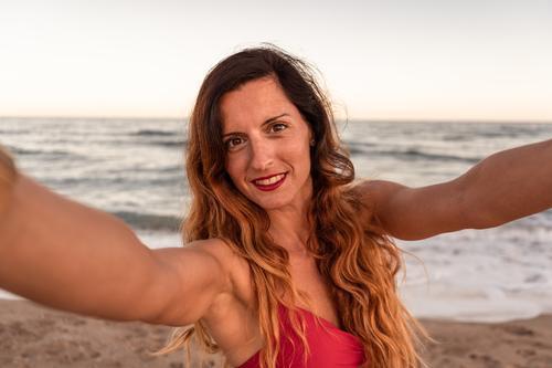Hübsche stilvolle Frau, die Spaß hat, ein Selfie am Strand bei Sonnenuntergang zu machen. MEER Sommer Glück Fotokamera Natur im Freien Lifestyle verwenden