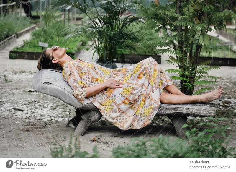 Frau im Kleid liegt entspannt auf einer Holzliege in einem Garten schön liegen entspannen Liege Urlaub chillen relaxen Sommer Reise Gemüsebeet Pflanzen grün