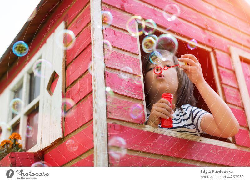 Junge bläst Seifenblasen in einem hölzernen Spielhaus Holz rot Schweden Haus Baum Baumhaus Sommer im Freien Abenteuer spielerisch echte Menschen einfaches Leben