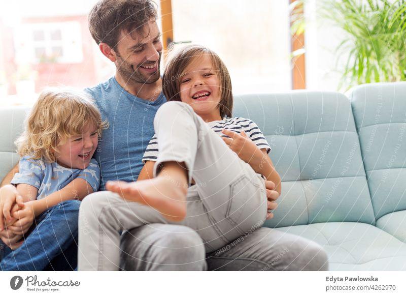 Vater spielt mit seinen kleinen Söhnen zu Hause Mann Papa Familie Eltern Verwandte Sohn Junge Kinder Partnerschaft Zusammensein Zusammengehörigkeitsgefühl Liebe