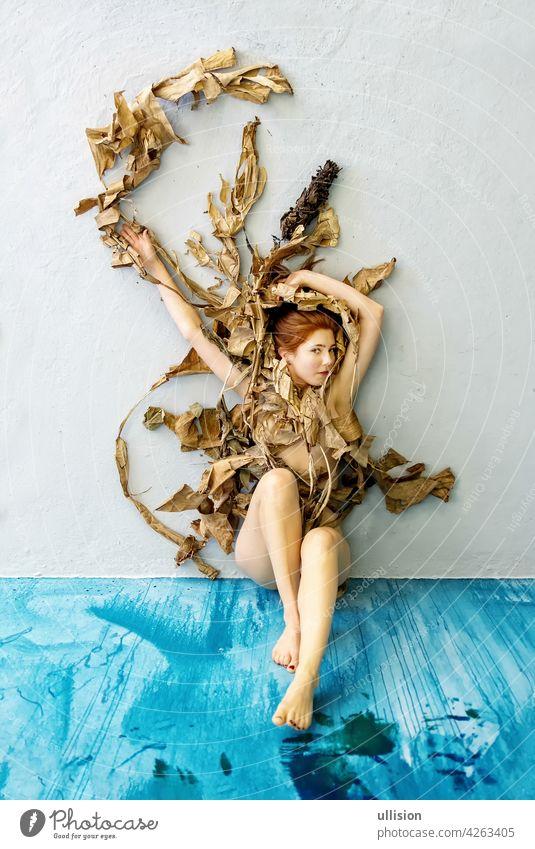 Junge sexy Frau mit roten Haaren kunstvoll mit trockenen, verwelkten dekorative Bananenbaum Blätter auf dem blauen Boden sitzen. kopieren Raum Behaarung Baum