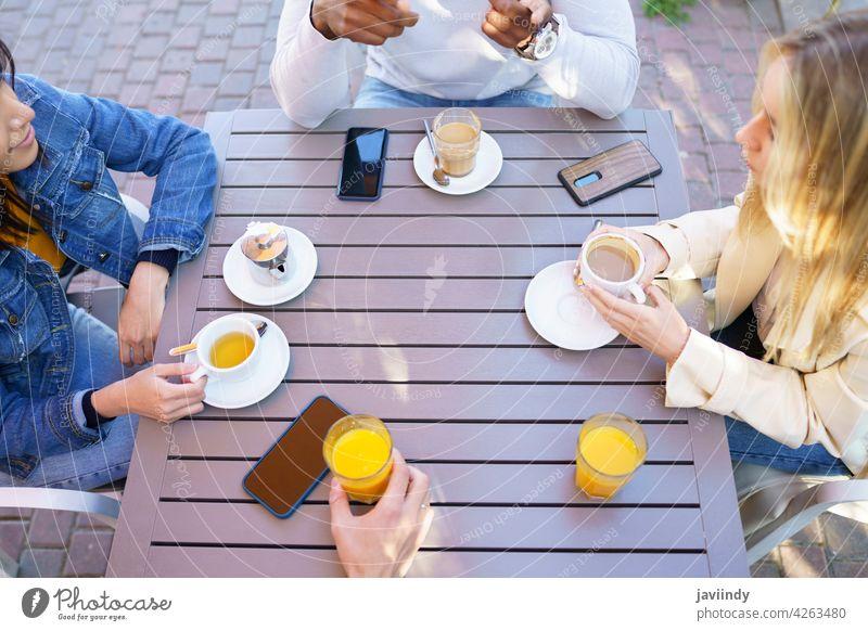 Draufsicht auf Menschen, die am Tisch auf der Terrasse einer Bar sitzen und einige Getränke trinken. Kaffee Café Tasse Freunde Tee unkenntlich Sitzung