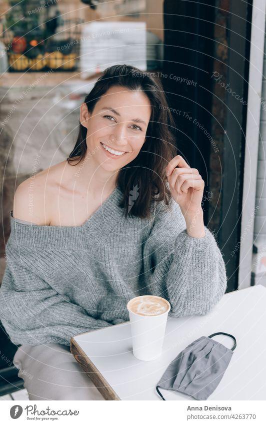 Junge Dame trinkt Kaffee im Cafe Tasse Frau Porträt trinken jung Gesichtsmaske Lächeln Sperrung angehoben schön lässig brünett Tisch Glück Person Erwachsener