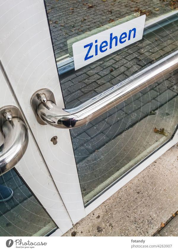Verriegelte Glastür Objekt Außenseite Detailansicht verschlossen Tür Ladentür Eingang hinweisschild ziehen niemand Draussen aussenansicht deutsche Sprache