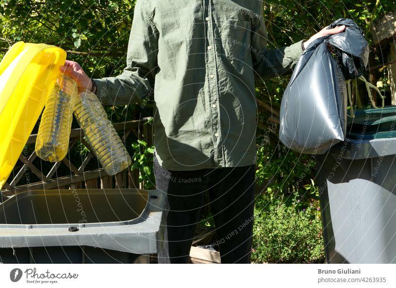 Eine Person, die eine selektive Sortierung von Hausmüll in Recycling-Behältern durchführt. Mann, der Plastikflaschen in einen gelben Behälter und Müll in einem Sack in einen grünen Behälter wirft.