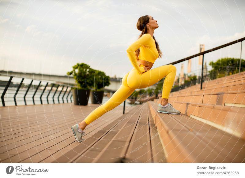 Junge Frau streckt sich am Flussufer jung Joggen Training Fitness nach oben Läufer Athlet Menschen Lifestyle Gesundheit Person Körper Sommer Beine