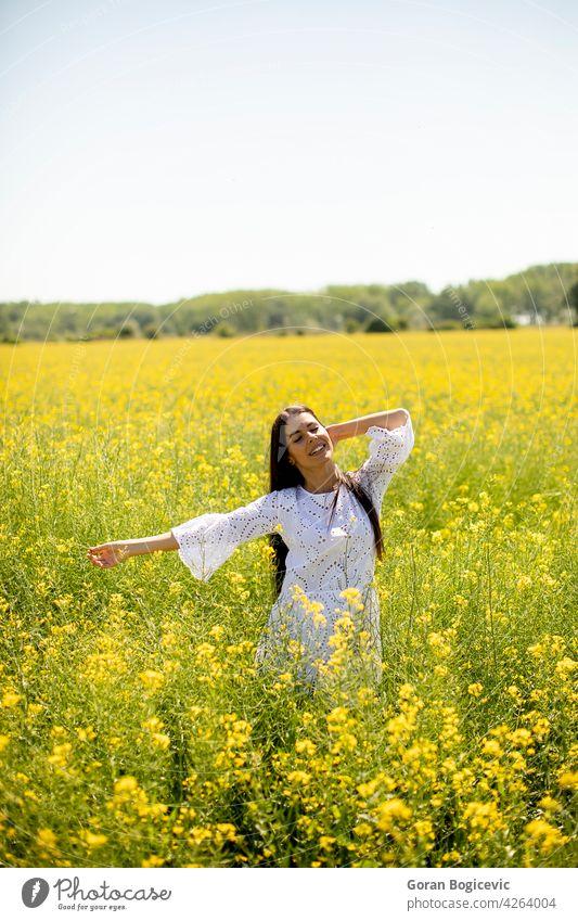 Junge Frau auf dem Rapsfeld schön Feld außerhalb gelb Sommer im Freien Schönheit Glück Frühling Person Wiese Natur Blume Freiheit Lifestyle sonnig geblümt