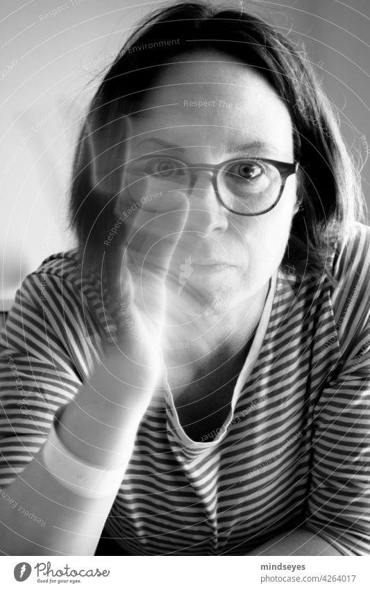 Frau mit Brille winkt Porträt Schwarzweißfoto Streifenpullover Bewegungsunschärfe winken winkende Hand Blick in die Kamera Blick nach vorn ernst ruhig Mensch