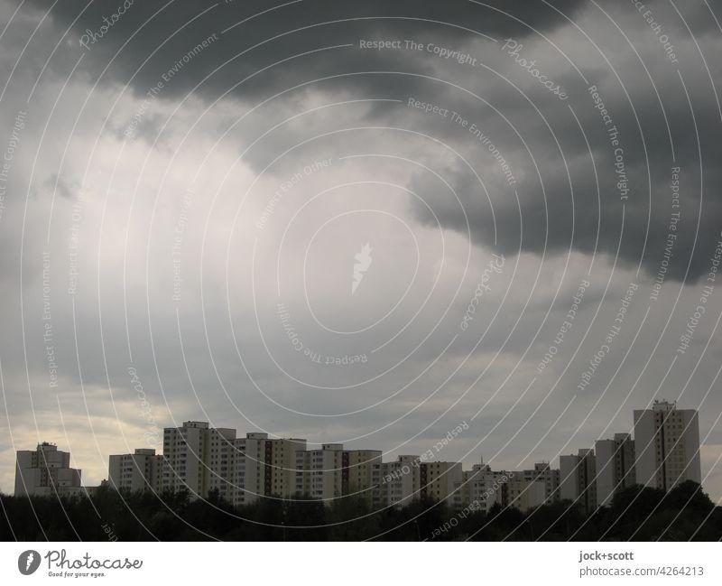 Auf und Ab bei den Immobilien und das düstere Klima zeigt leichte Aufhellungen Himmel schlechtes Wetter Wohnhochhaus Stimmung trist Gedeckte Farben Silhouette