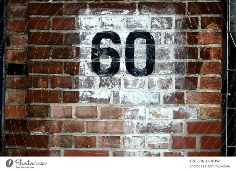 Die Zahl 60 (sechzig) wurde in großen schwarzen Ziffern auf nachlässig weiß getünchtem Quadrat  an die rotbraune Backsteinwand eines alten Gebäudes gemalt und stellt vielleicht eine Hausnummer dar