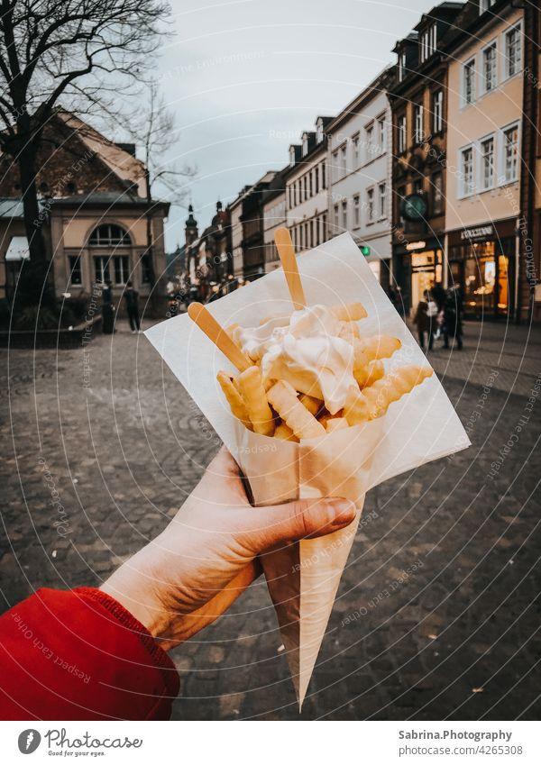 Eine Portion Pommes Frites mit Mayonnaise in der linken Hand in der Hauptstraße, Heidelberg Pommes frites Essen Fastfood Lebensmittel Fett Baden-Württemberg
