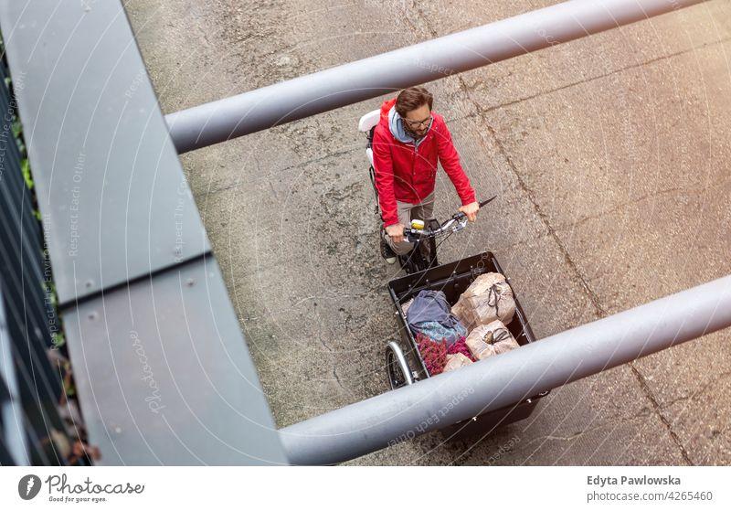 Mann auf dem Rückweg vom Einkaufen mit einem Lastenfahrrad tragen Dreirad Lastenrad Tag Gesundheit Lifestyle aktiv im Freien Freude Fahrrad Zyklus Radfahren