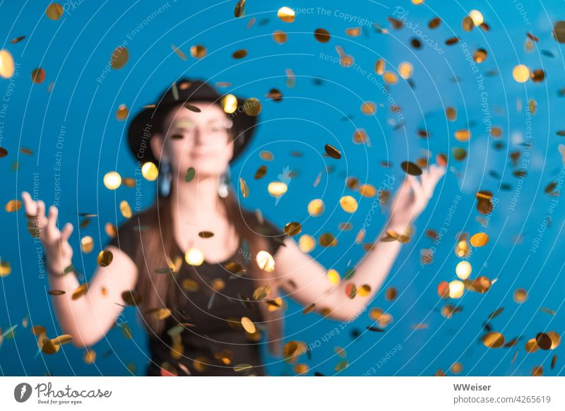 Eine junge Frau mit Hut freut sich über den glitzernden Goldregen Münzen Schatz Goldmarie reich Glück Erfolg Geld Reichtum Gewinn Belohnung feiern froh freuen