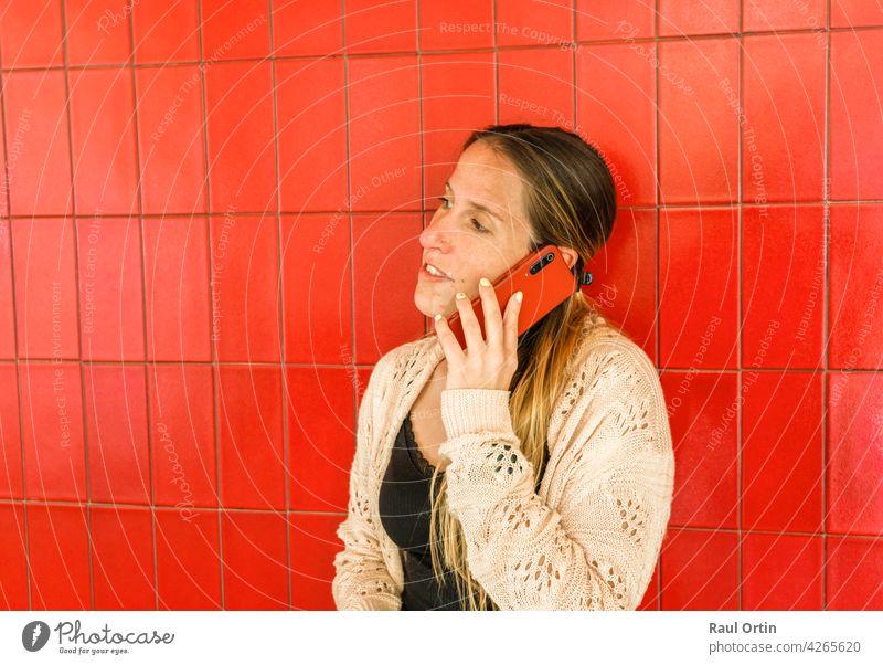 Frau spricht am Handy auf rotem Hintergrund. weiblich mit Telefon, einen Anruf tätigen, Technologie Lebensstil. Person Technik & Technologie Lifestyle
