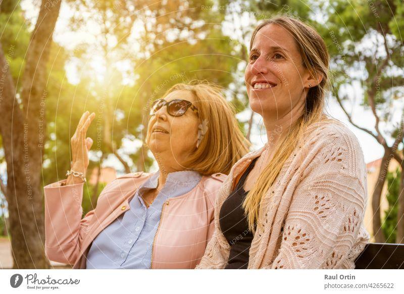 Ältere Mutter und ihre erwachsene Tochter reden und genießen die Zeit zusammen in der Natur Park bei Sonnenuntergang. Frauen Glück Familie jung alt sprechend