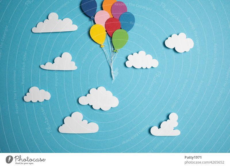 Aus Papier ausgeschnittene Luftballons schweben zwischen fluffigen Wolken durch den Himmel aus dem Bild herausl viele wolken aufsteigen verlassen fliegen