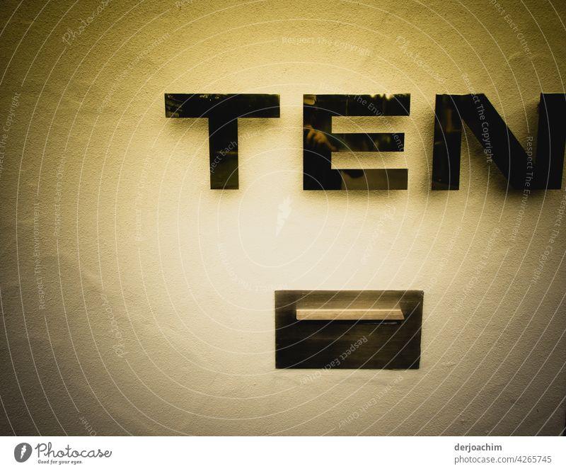 Hausnummer T E N , mit darunter liegendem Briefkasten.  Die Hauswand im zarten Gelb. Die Buchstaben und der Einwurf  ist in Schwarz gehalten. Nummer