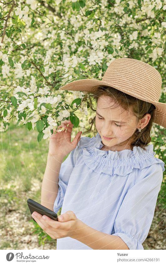 Cute schöne lächelnde Mädchen in einem Strohhut schießt Inhalte für soziale Netzwerke auf einem Smartphone. Frühling Fotorahmen vor dem Hintergrund der blühenden Apfelbäume. Glückliches Kind. Vertikale Aufnahme