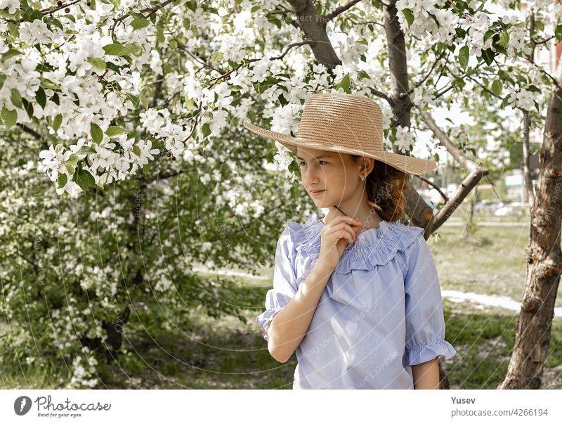 Porträt eines niedlichen, nachdenklichen Mädchens mit Strohhut in einem blühenden Garten. Frühling Fotoaufnahme vor dem Hintergrund der blühenden Apfelbäume. Glückliches Kind. Platz kopieren